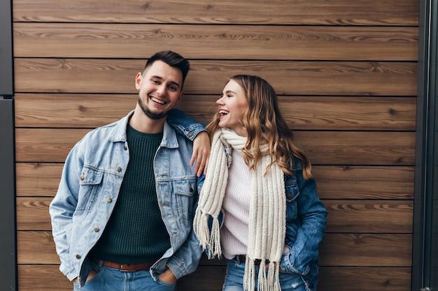 Betoverend meisje dat in witte sjaal vriendje met liefde bekijkt. indoor portret van knappe europese man vrije tijd doorbrengen met schattige vriendin.