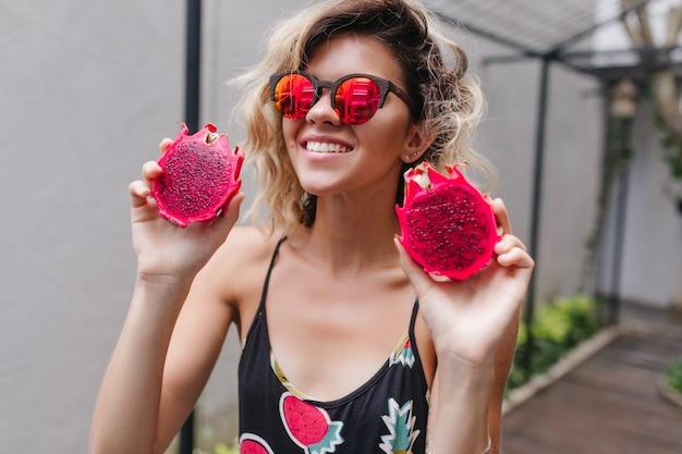 Betoverend meisje draagt roze zonnebril met sappige pitaya. portret van charmante glimlachende vrouw die exotisch fruit eet.