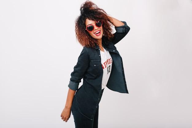 Betoverend meisje in rode zonnebril poseren met hand omhoog. modieus vrouwelijk model lachen met afrikaanse kapsel genieten.
