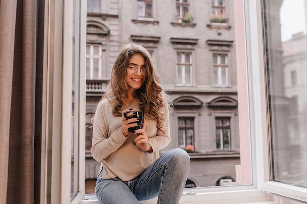 Betoverend meisje in stijlvolle spijkerbroek zittend op vensterbank met koffie