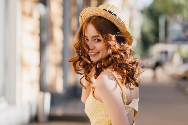Betoverend meisje met donker krullend haar gek rond buiten in warme zomerdag. geweldig gember vrouwelijk model in hoed en gele jurk lachen op stedelijke straat.