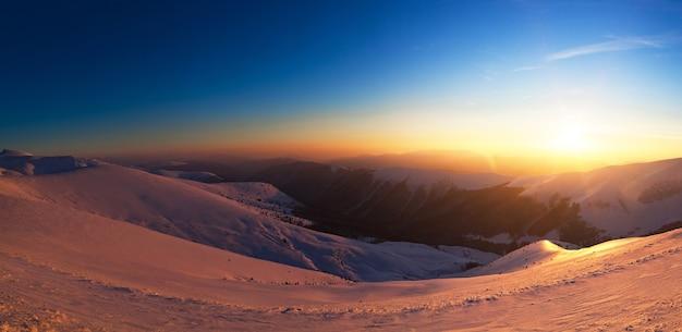 Betoverend mooi uitzicht op de bergen en heuvels in de besneeuwde vallei in de late avond