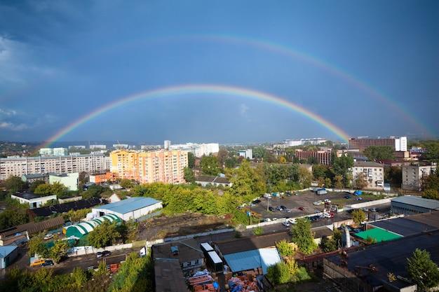 Betoverend panorama van een europese stad met een grote mooie regenboog tegen een achtergrond van blauwe wolken en zonnestralen. concept van een natuurlijk fenomeen. advertentie ruimte