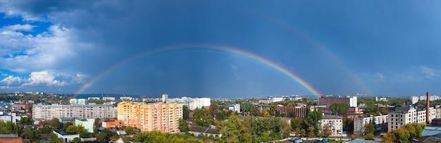 Betoverend panorama van een europese stad met een grote prachtige regenboog