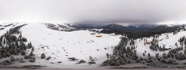 Betoverend prachtig panorama van bergen en heuvels bedekt met dennenbomen op een bewolkte winterse dag