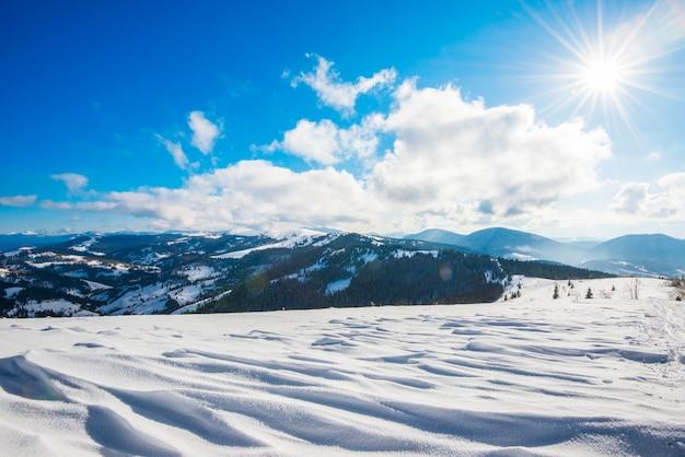 Betoverend uitzicht op berghellingen met dicht struikgewas van bomen en sneeuwbanken tegen de lucht