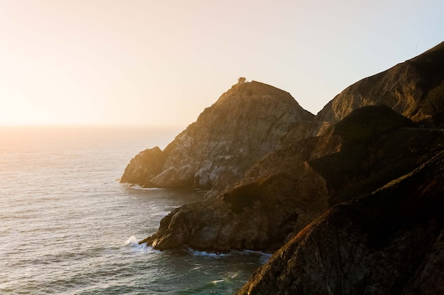 Betoverend uitzicht op de kalme oceaan en de kliffen aan de kust onder de blauwe lucht tijdens zonsondergang