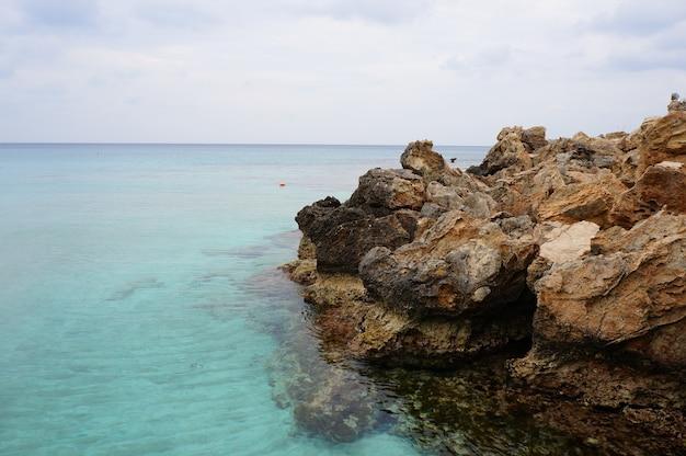Betoverend uitzicht op de oceaan en de rotsen op het strand onder de blauwe lucht