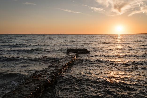 Betoverend uitzicht op de oceaan en een pier onder kleurrijke hemel tijdens zonsondergang in dalmatië, kroatië