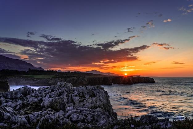 Betoverend uitzicht op de oceaan, omringd door rotsachtige bergen tijdens zonsondergang