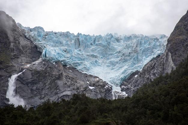 Betoverend uitzicht op de rotsachtige bergen met een waterval