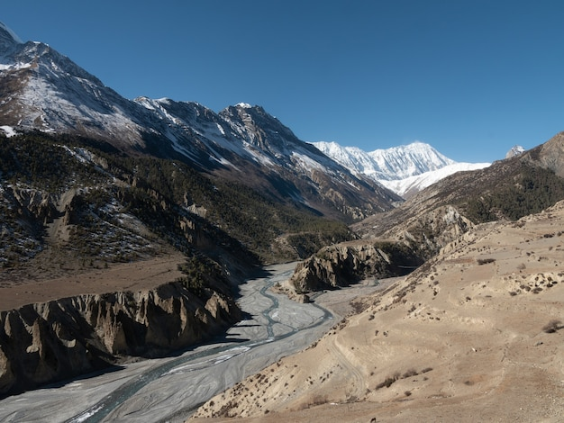 Betoverend uitzicht op de waterstromen door de met sneeuw bedekte bergen in nepal