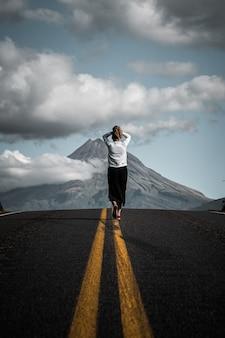 Betoverend uitzicht op een jonge toerist die op de lege weg loopt die naar de berg leidt