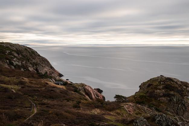 Betoverend uitzicht op een kalme oceaan, omringd door rotsachtige bergen op een bewolkte dag