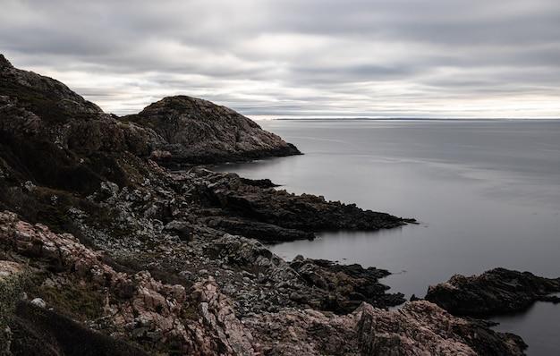 Betoverend uitzicht op een rotsachtige kust en een kalme zee op een sombere dag