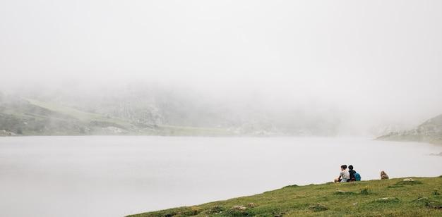 Betoverend uitzicht op het mistige meer met zittende mensen