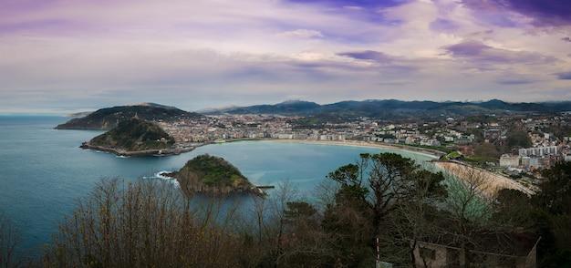 Betoverend uitzicht over de stad langs de kustlijn op een bewolkte dag met een weelderige natuur