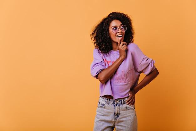 Betoverend zwartharig meisje poseren met plezier op oranje. optimistisch vrouwelijk model glimlachen.
