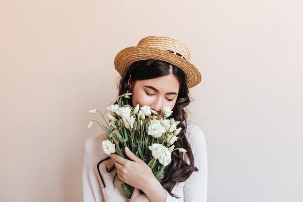 Betoverende aziatische vrouw die witte bloemen snuift. studio shot van chinese vrouw met eustomas geïsoleerd op beige achtergrond.
