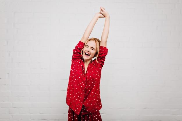 Betoverende blonde vrouw in rode nachtkleding die zich uitstrekt over lichte muur met glimlach. leuk europees meisje in pyjama's genieten van goedemorgen en lachen.