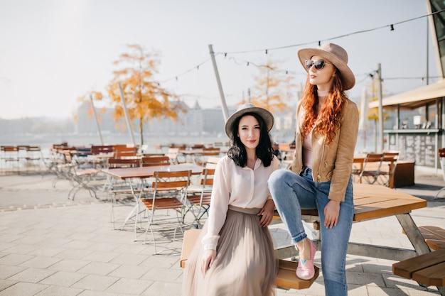Betoverende brunette vrouw in lange rok zittend op terras met vriendin in stijlvolle hoed