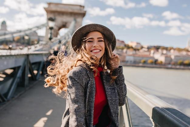Betoverende dame met prachtig krullend haar poseren met plezier op de brug in winderige dag
