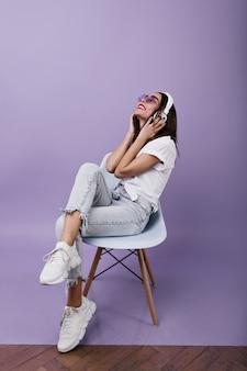 Betoverende europese vrouw in witte sneakers muziek luisteren. portret van gelukkig meisje met bruin haar, zittend op een stoel met koptelefoon.