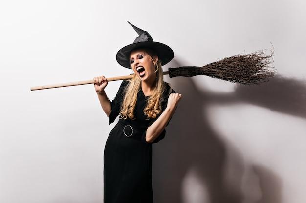 Betoverende heks in zwarte outfit die van feestje geniet. geweldige blonde tovenaar met bezem.