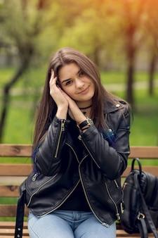 Betoverende jonge kaukasische vrouw in zwarte lederen jas zitten in het park op de bank