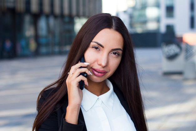 Betoverende jonge onderneemster die op haar celtelefoon spreekt, die openlucht camera bekijkt. het mooie oostelijke kaukasische brunette met grote lippen en lange spijkers die gesprek hebben, roept smartphone op.