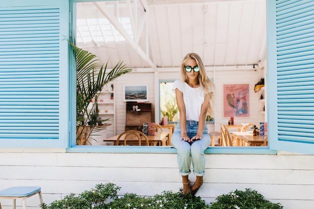 Betoverende jonge vrouw die in blauwe jeans op vensterbank zit.