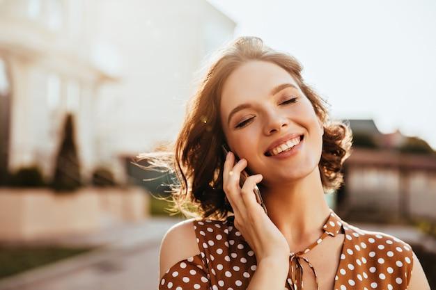 Betoverende jonge vrouw die over telefoon spreekt met gesloten ogen. buiten schot van vrij kaukasisch meisje met kort bruin haar.