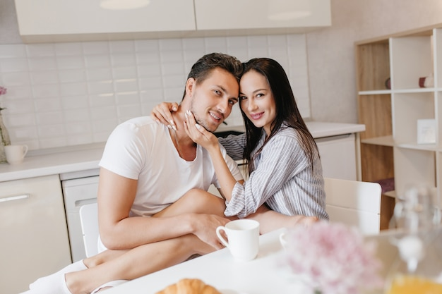 Betoverende jonge vrouw zittend op de knieën van vriendje terwijl hij koffie drinkt