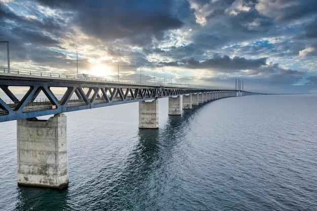 Betoverende luchtfoto van de brug tussen denemarken en zweden onder de bewolkte hemel