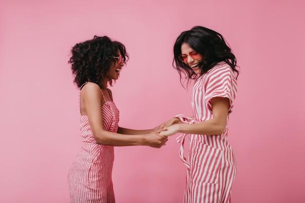 Betoverende meisjes die samen grappen maken tijdens het poseren. vrij afrikaanse vrouw hand in hand met vriend en dansen.