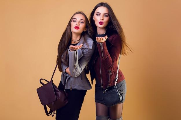 Betoverende mooie vrouwen die een kus blazen en casual winterjassen dragen