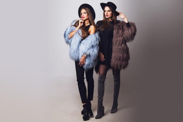Betoverende mooie vrouwen die en bontjassen stellen dragen