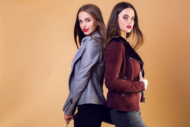 Betoverende mooie vrouwen poseren en dragen casual winterjassen