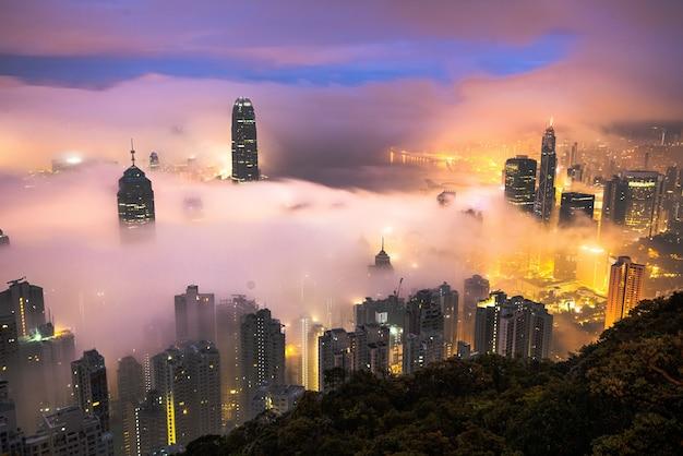 Betoverende opname van de wolkenkrabbers van een stad die 's nachts in mist is gehuld