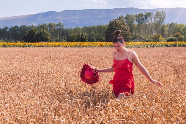 Betoverende opname van een aantrekkelijke vrouw in een rode jurk die voor de camera in een tarweveld poseert