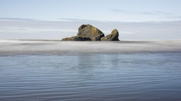 Betoverende opname van een enorme rots met oceaan