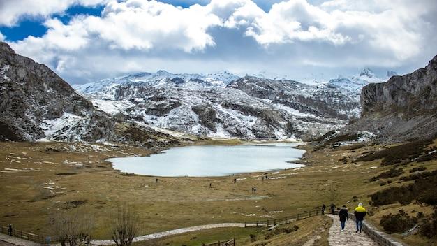 Betoverende opname van een natuurlijk landschap met een meer, besneeuwde bergen en grote pluizige wolken