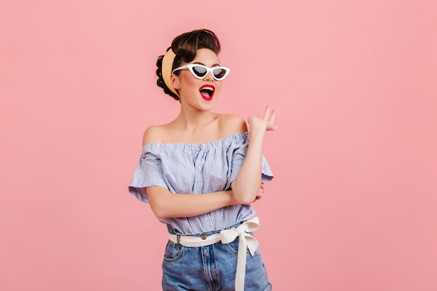 Betoverende pinup meisje poseren in zonnebril. studio shot van slanke jonge dame in gestreepte blouse geïsoleerd op roze achtergrond.