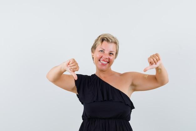 Betoverende vrouw die duim in zwarte blouse vooraanzicht toont.
