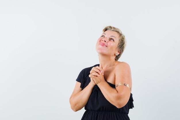 Betoverende vrouw die gecombineerde handen op haar borst houdt terwijl zij in zwarte blouse wenst en hoopvol kijkt. vooraanzicht.