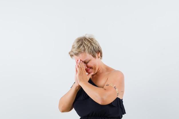 Betoverende vrouw die gecombineerde handen op haar voorhoofd houdt terwijl zij in zwarte blouse wenst en hoopvol kijkt