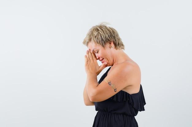 Betoverende vrouw die gecombineerde handen op haar voorhoofd houdt terwijl zij in zwarte blouse wenst.