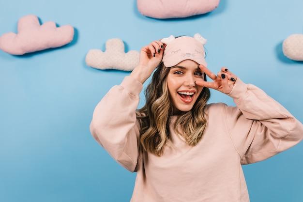 Betoverende vrouw die in slaapmasker op blauwe muur lacht