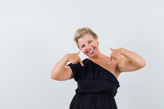 Betoverende vrouw die in zwarte blouse naar beneden wijst en vrolijk kijkt. vooraanzicht.