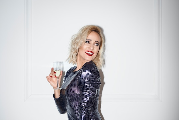 Betoverende vrouw die met champagne exemplaarruimte bekijkt